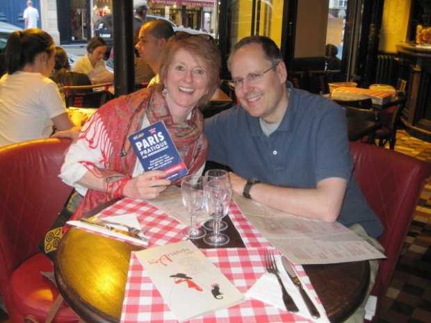 Colleen in a Paris cafe with Erik holding the street by arrondissement book Paris Pratique