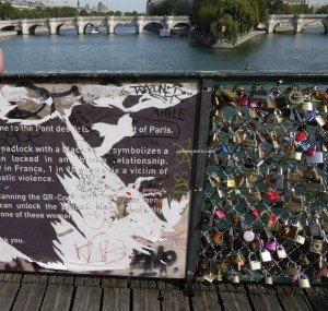 Padlocks and sign on Pont des Arts. Sign is a caution about domestic violence is torn and filled with grafitti.