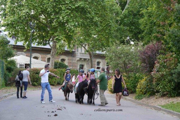 Children wearing helmets on ponies at Jardin d'Acclimatation in Paris