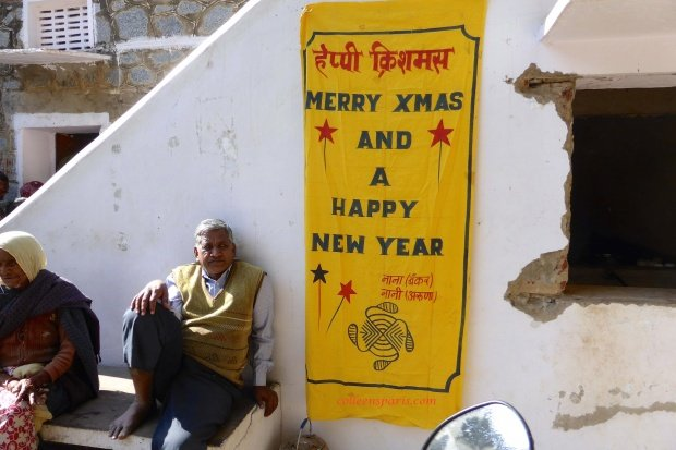 Barefoot college, Tilonia, India, man sitting next to Merry Xmas/Happy New Year banner
