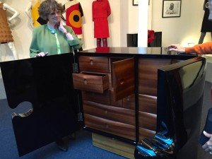 Renee Tapoinier showing us a chest of drawers included in the Pierre Cardin collection