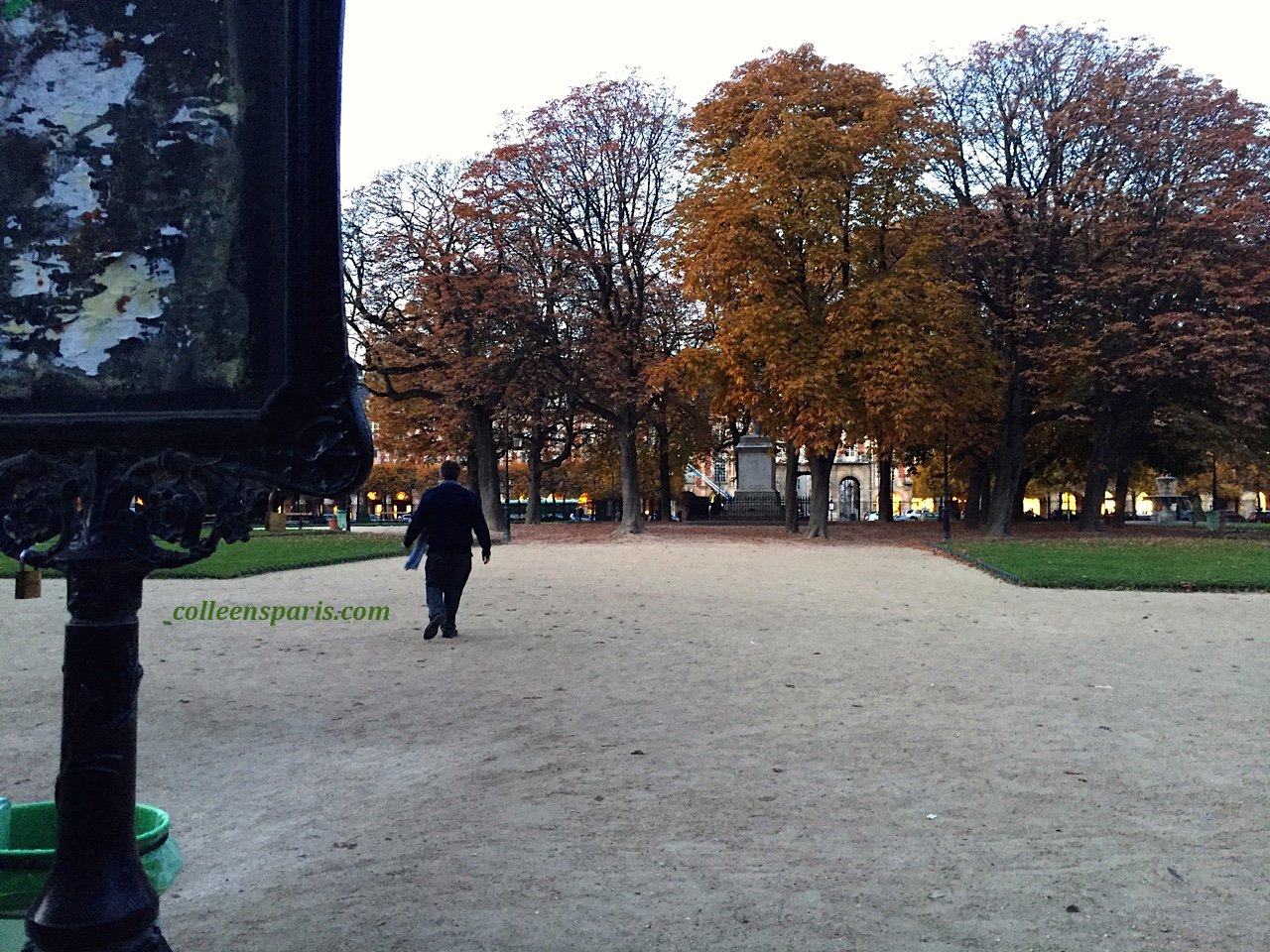 The gardien ending his day at Square Louis XIII - Place des Vosges in the 4th arrondissement of Paris walking toward the statue.