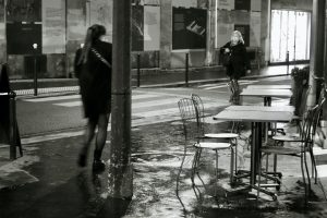 Silhouette, near and far and movement as two women walk toward each other past a café